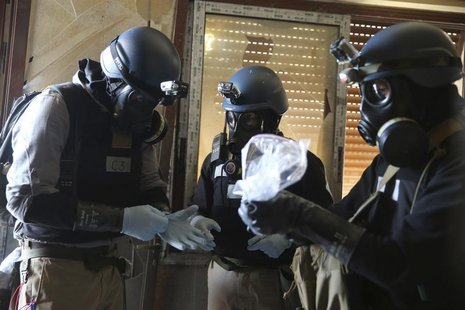 A U.N. chemical weapons expert, wearing a gas mask, holds a plastic bag containing samples from one of the sites of an alleged chemical weap