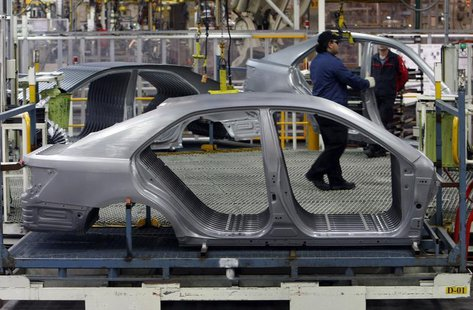 An Auto worker loads bodyshells of a Toyota Camry Hybrid car onto the assembly line at the Toyota plant in Melbourne August 31, 2009. REUTER