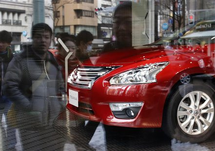 Nissan Motor's Teana sedan is displayed as pedestrians are reflected in a window at the company's showroom in Tokyo February 10, 2014. REUTE