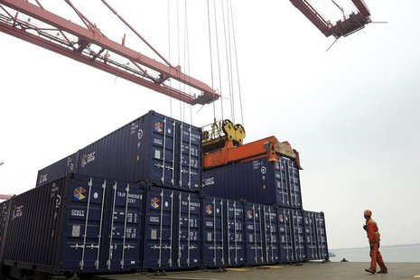 A worker stands near a crane unloading shipping containers from a cargo ship at a port in Lianyungang, Jiangsu province November 8, 2013. RE