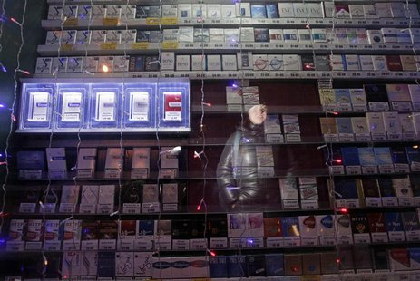 A woman is reflected in a window displaying packs of cigarettes on a street in Russia's Siberian city of Krasnoyarsk January 24, 2013. REUTE