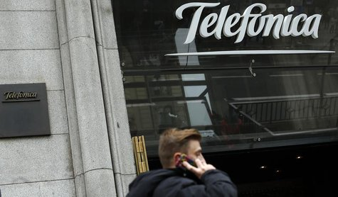 A man talks on a mobile phone as he walks past Spanish telecom group Telefonica flagship store in central Madrid November 8, 2013. REUTERS/S