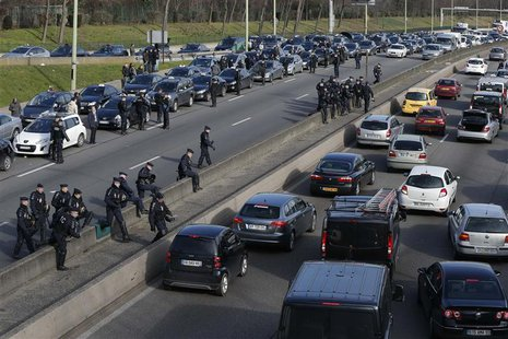 French gendarmes secure the Paris ring road as taxi drivers on strike block the traffic during a protest in Paris February 10, 2014. REUTERS