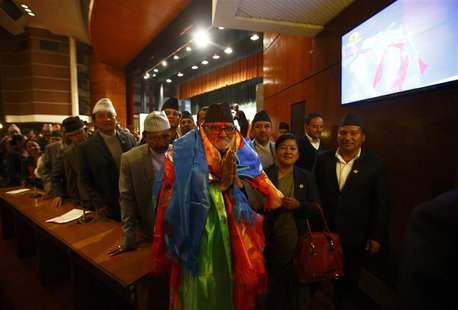Newly elected Nepalese Prime Minister Sushil Koirala greets media personnel as he walks out from the Parliament after being elected as the P