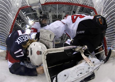 Team USA's Jocelyne Lamoureux (17) crashes into Switzerland's goalie Florence Schelling (R) as Switzerland's Laura Benz defends during the t