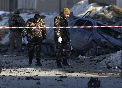 Afghan security personnel investigate at the site of a suicide bomb attack in Kabul, February 10, 2014. REUTERS/Omar Sobhani