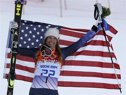 Third-placed Julia Mancuso of the U.S. celebrates with a U.S. flag during the flower ceremony after the women's alpine skiing super combined