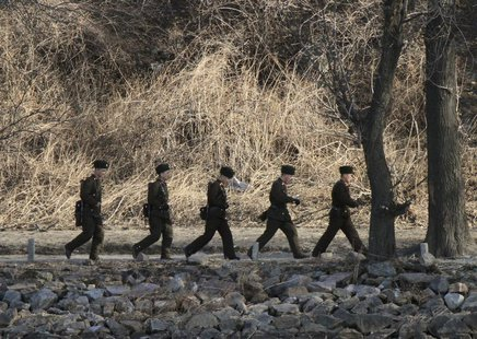 North Korean soldiers patrol along the bank of Yalu River near the North Korean town of Sinuiju, opposite the Chinese border city of Dandong