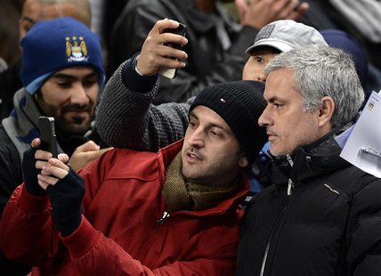 Chelsea manager Jose Mourinho (R) has his photograph taken with fans before their English Premier League soccer match against Manchester Cit