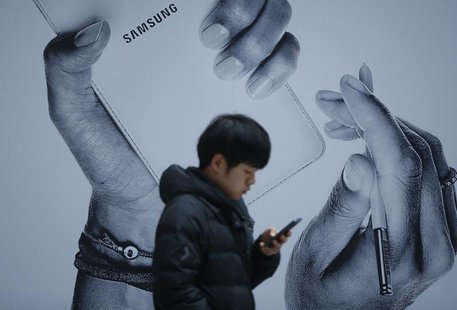 A passenger using his mobile phone walks past an advertisement promoting Samsung Electronics' Galaxy Note 3 at its exhibition hall at a rail