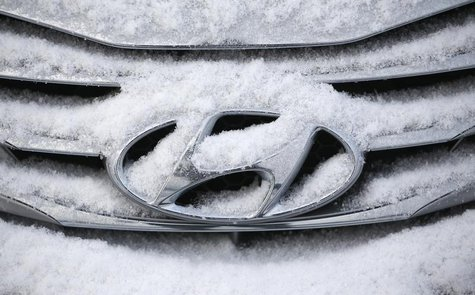 The logo of Hyundai Motor on a sedan is covered with snow at a shipping yard of South Korea's biggest automakers Hyundai Motor Co and affili