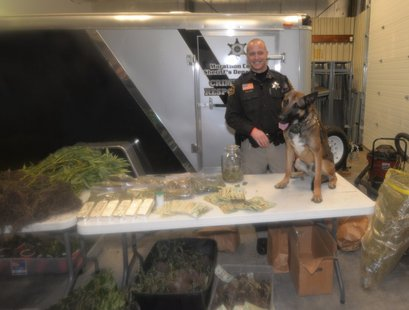Marathon County Deputy Sheriff Brandon Stroik and his K-9 partner Csibi pose with drugs seized in a series of arrests, February 10 2014