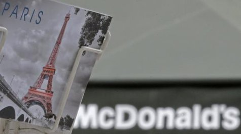 A postcard showing the Paris city landmark, the Eiffel Tower, is seen in front of a McDonald's fast-food restaurant in Paris, January 22, 2014. CREDIT: REUTERS/CHRISTIAN HARTMANN