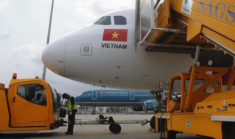 A worker pumps fuel into a Vietjet Air A320 aircraft, in front of a Vietnam Airlines aircraft at Tan Son Nhat airport in Vietnam's southern