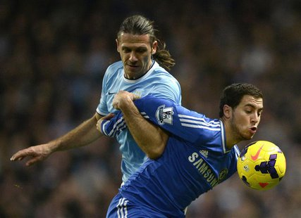 Chelsea's Eden Hazard (R) is challenged by Manchester City's Martin Demichelis during their English Premier League soccer match at the Etiha