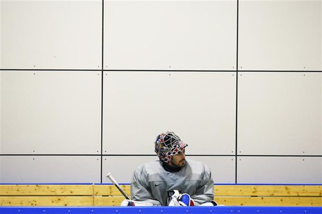 The U.S. men's hockey team goaltender Ryan Miller sits on the bench during a team USA practice at the 2014 Sochi Winter Olympics February 11