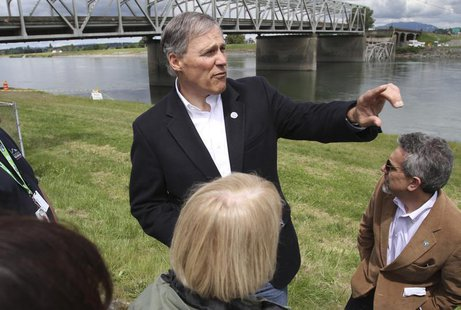 Washington State Governor Jay Inslee looks over the scene as a span of highway bridge sits in the Skagit River May 24, 2013 after collapsing