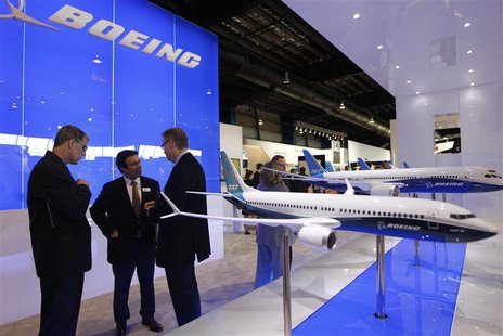 Visitors talk at the Boeing booth at the Singapore Airshow February 11, 2014. REUTERS/Edgar Su