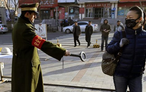A pedestrian reacts as a security officer holds out a detector on a street in Urumqi, Xinjiang Uighur autonomous region, November 17, 2013.