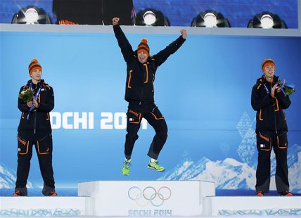 Gold medalist Sven Kramer (C) of the Netherlands jumps on the podium next to his compatriots silver medalist Jan Blokhuijsen (L) and bronze