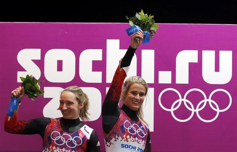 Winner Germany's Natalie Geisenberger (R) and second-placed compatriot Tatjana Huefner celebrate with their bouquets at the flower ceremony