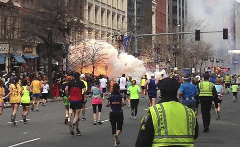 Runners continue to run towards the finish line of the Boston Marathon as an explosion erupts near the finish line of the race in this photo