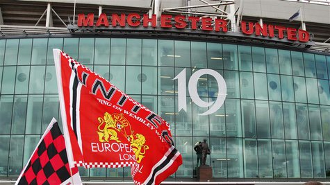 Manchester United supporters wave flags outside the stadium before their English Premier League soccer match against Blackpool at Old Traffo
