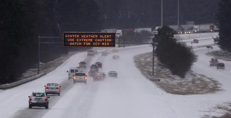 Cars drive under a traffic sign displaying winter storm warnings after a rare snowstorm in Kennesaw, Georgia, January 28, 2014. REUTERS/Tami