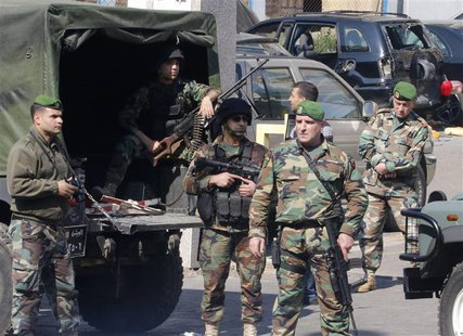 Lebanese army soldiers stand near a booby-trapped car (black, in background) loaded with explosives in the Corniche al-Mazraa district of ce
