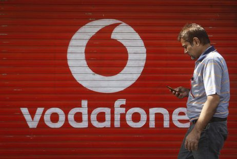 A man checks his mobile phone as he walks past a shop displaying the Vodafone logo on its shutter in Mumbai January 15, 2014. REUTERS/Danish