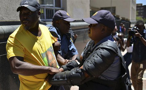 A police officer detains an African National Congress (ANC) supporter after they tried to confront members of the opposition Democratic Alli