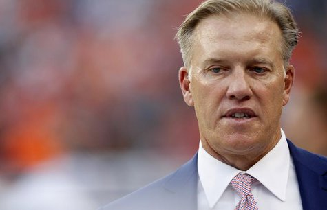 Denver Broncos Executive Vice President of Football Operations John Elway walks on the field before their NFL football game against the Balt
