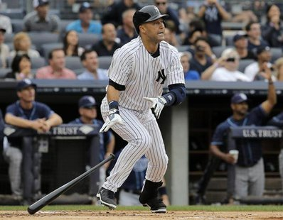 New York Yankees batter Derek Jeter drops the bat and watches the ball as he hits a two-run home run on the first pitch from Tampa Bay Rays