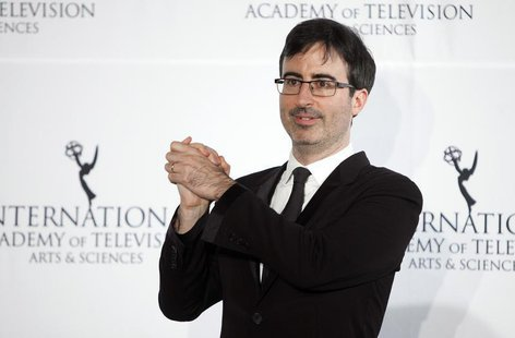 Comedian John Oliver poses for photographers backstage during the 41st International Emmy Awards in New York, November 25, 2013. REUTERS/Car