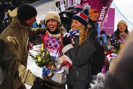 Gold medalist Kaitlyn Farrington (C) of the U.S. celebrates with her parents Gary and Suze Farrington after winning the women's snowboard ha