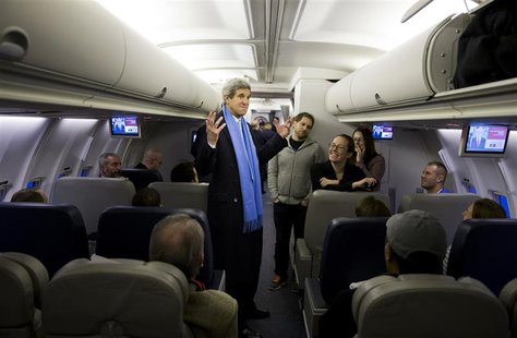 U.S. Secretary of State John Kerry (C) talks with reporters on a plane at Andrews Air Force Base, Maryland before departing for South Korea