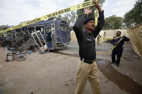 A security official uses a tape to cordon off a site of a damaged police bus after an explosion in Karachi February 13, 2014. REUTERS/Athar