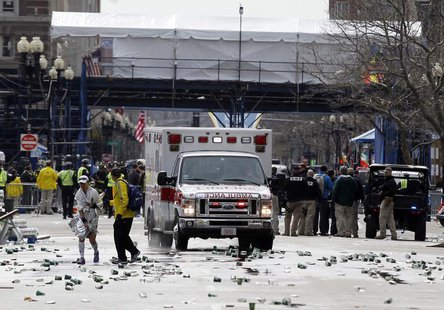 A runner is escorted from the scene after explosions went off at the 117th Boston Marathon in Boston, Massachusetts April 15, 2013. REUTERS/
