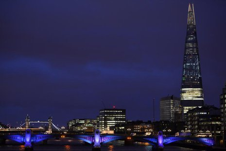 The Shard Building skyscraper (R) is seen with Tower Bridge (L) at dusk in London December 18, 2013. REUTERS/Toby Melville