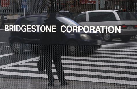 A man is reflected in a signboard of Bridgestone Corp at the company's headquarters in Tokyo February 18, 2011. REUTERS/Toru Hanai
