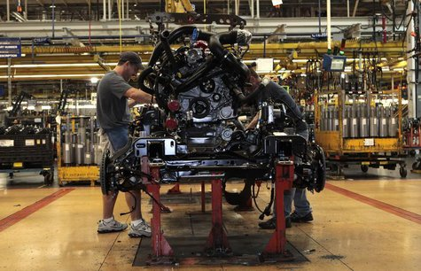 Ford Motor auto assembly workers install an EcoBoost fuel efficient engine in the chassis of a 2014 F-150 pick-up truck at the Dearborn Truc