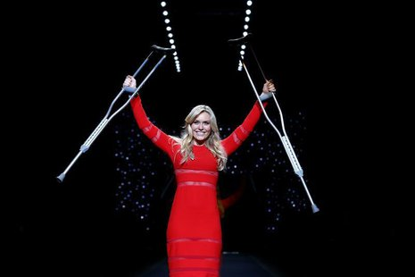 Olympic downhill champion Lindsey Vonn raises her crutches as she presents a creation by Cynthia Rowley for the The Heart Truth Fall 2014 co