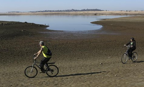 Visitors ride bicycles near the receding waters at Folsom Lake, which is 17 percent of its capacity, in Folsom, California January 22, 2014.