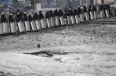 Riot police stand guard near barricades built at the site of recent clashes with anti-government protesters in Kiev February 13, 2014. REUTE