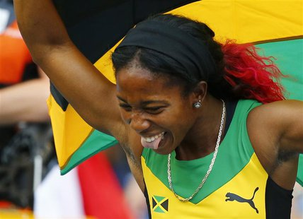 Shelly-Ann Fraser-Pryce of Jamaica holds her national flag after winning the women's 4x100 metres relay final during the IAAF World Athletic