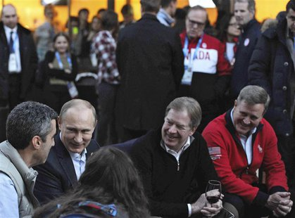 Russia's President Vladimir Putin (2nd L) sits next to to United States Olympic Committee (USOC) chairman Larry Probst (2nd R) as he visits