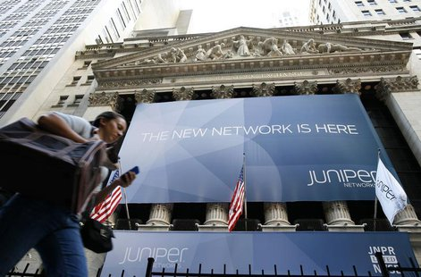 A woman walks past a banner with the logo of Juniper Networks Inc. covering the facade of the New York Stock Exchange, October 29, 2009. REU