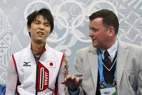 "Japan's Yuzuru Hanyu reacts with coach Brian Orser in the ""kiss and cry"" area during the Figure Skating Men's Free Skating Program at the So"