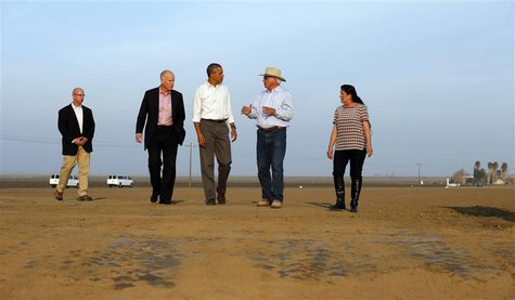 U.S. President Barack Obama walks with farmers Joe Del Bosque and Maria Del Bosque as he tours a drought affected farm field in Los Banos, C