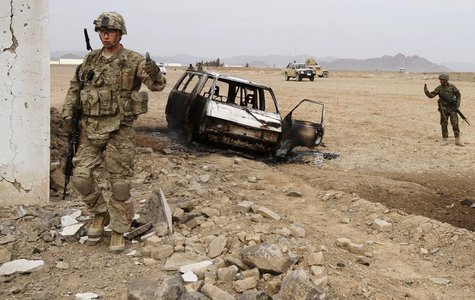 A U.S. soldier stands at the site of a suicide attack on a NATO base in Zhari, west of Kandahar province, January 20, 2014. REUTERS/Ahmad Na